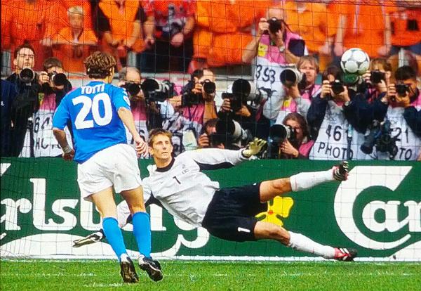 """Amsterdam, Amsterdam Arena, 29 giugno 2000. Nella semifinale degli Europei l'Italia elimina ai rigori i padroni di casa dell'Olanda, con un'epica partita difensiva in 10 contro 11 e sorretta dalle parate di Toldo, capace di neutralizzare ben 3 rigori di cui il primo nei tempi regolamentari. Il terzo rigorista azzurro è Francesco Totti, che spiazza Van der Sar con il primo (che da lì in poi diventerà leggendario) rigore """"a cucchiaio"""" della propria carriera"""