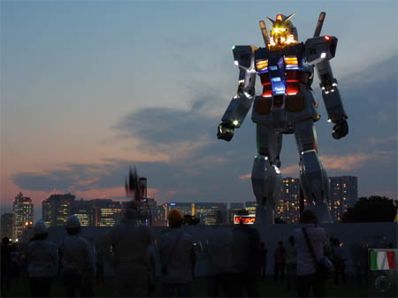 Un'immagine notturna del Gundam di Tokyo [http://www.hi-techitaly.com/news/varie/1115-gundam-compie-30-anni-e-arriva-a-tokyo-a-grandezza-naturale.html]